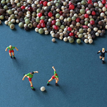 In Christopher Boffoli's photograph titled Peppercorn Soccer four tiny figurines of soccer players are captured mid game as they kick around a white peppercorn as if it were a soccer ball. They stand on a blue field in front of a sea of brown, red, white, and light green peppercorns.